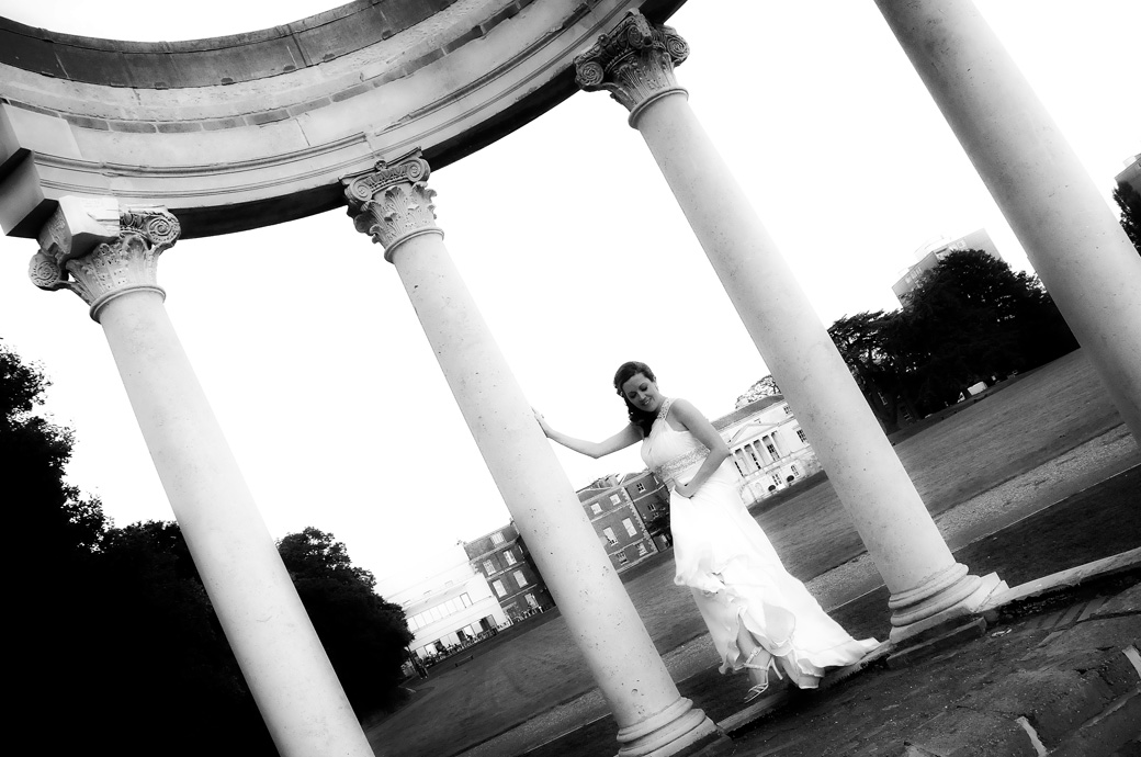 The bride dramatically posing by a restored temple columns wedding picture captured by London Lane wedding photography at Parkstead House