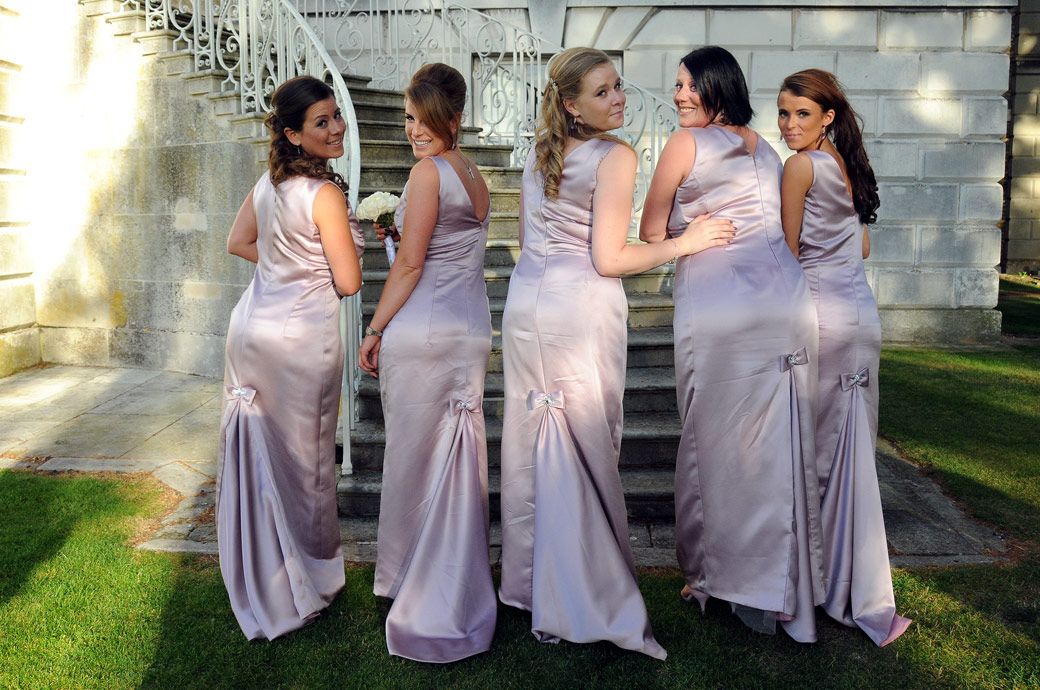 Bridesmaids turning round to show their bows wedding photo captured on the sweeping stone staircase of Parkstead House by London Lane wedding photography