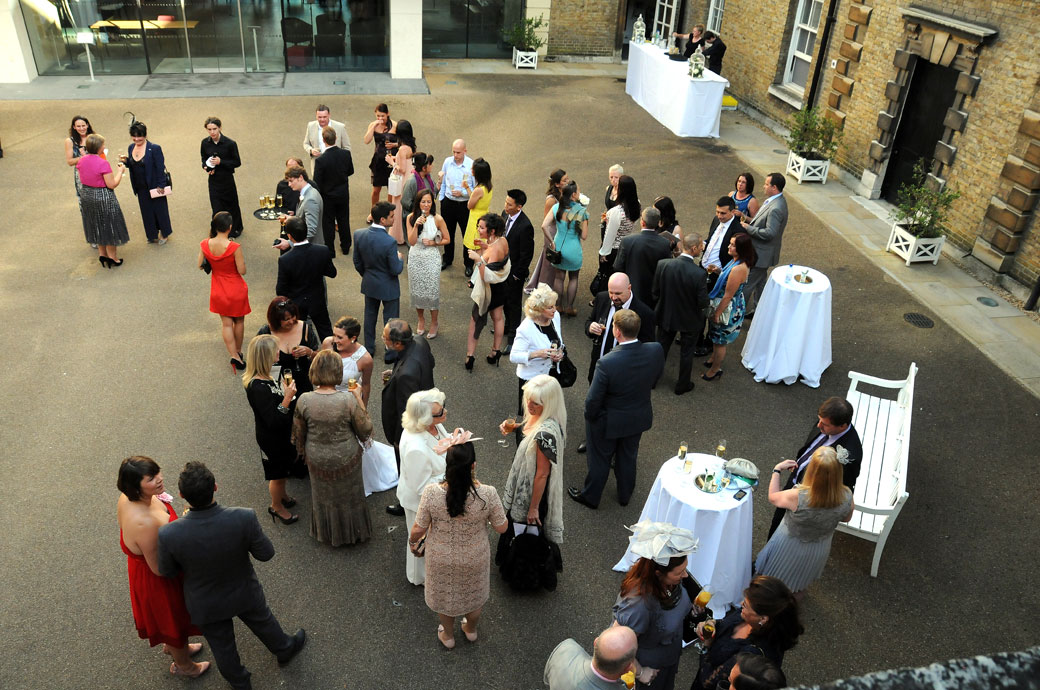 Celebrating wedding guests from the balcony wedding photo taken above the Victorian courtyard by London Lane wedding photography in Roehampton London at Parkstead House