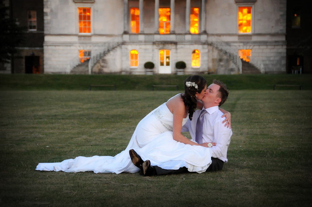A passionate kiss in front of glowing red windows wedding photograph taken on the lawn at sunset at Parkstead House captured by London Lane wedding photographers