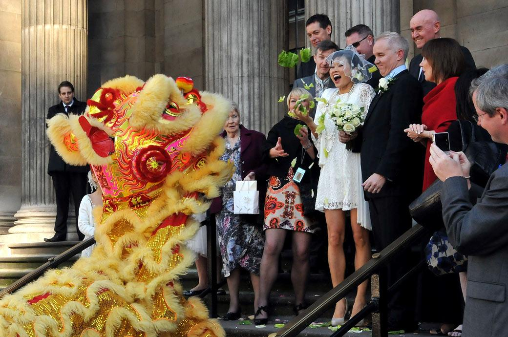 Newlyweds on steps of Westminster Register Office receive gifts of lucky cabbage in the traditional Chinese Lion dance wedding photographer London
