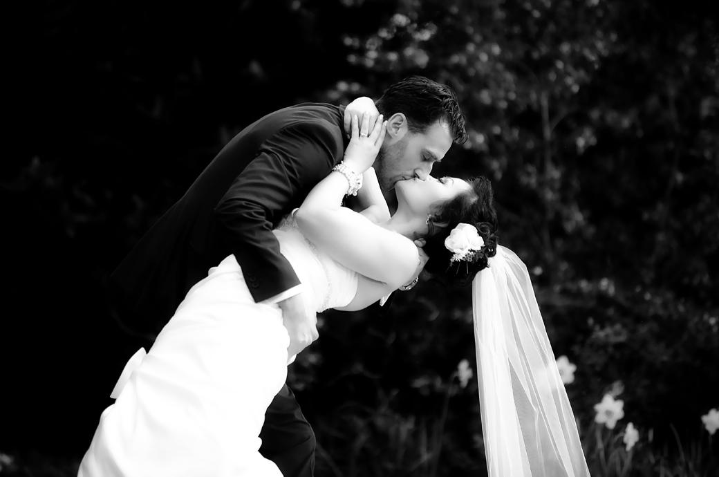 A stunningly beautiful and romantic newlywed kiss in the woods at Pembroke Lodge in Richmond wedding photographer London