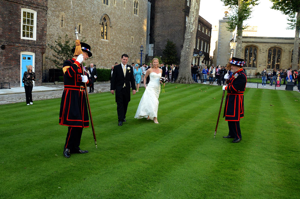 The Beefeaters await the newly-wed couple in this wedding photo taken on the lawn by The White Tower in the grounds of this fabulous London wedding venue wedding at The Tower of London