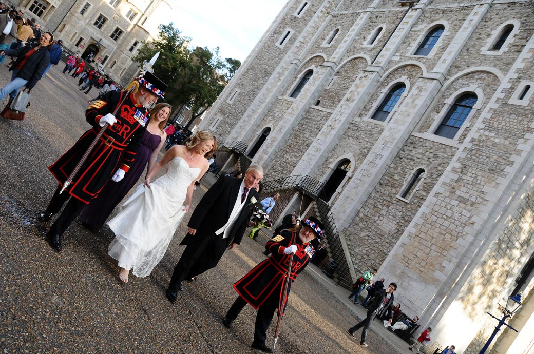 Bride and Beefeaters cracking a joke in this wedding photograph taken as they walk along the flagstones towards The Chapel Royal of St Peter ad Vincula at the Tower of London wedding venue