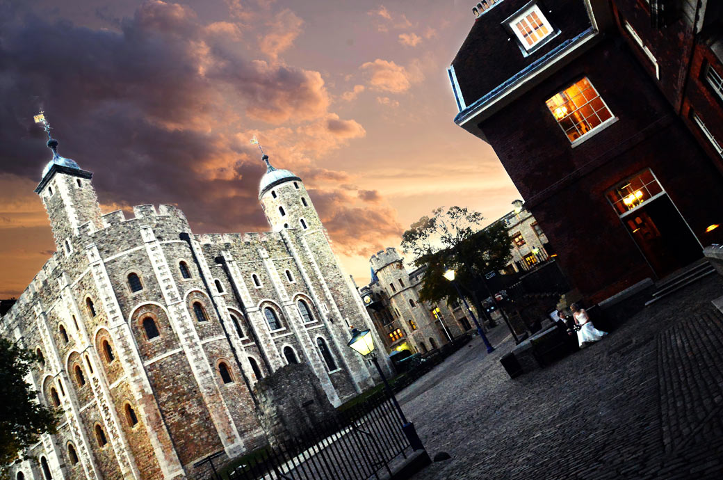 Wedding couple sit on a bench alone wedding picture taken at dusk outside the London wedding venue in the  at The Tower of London