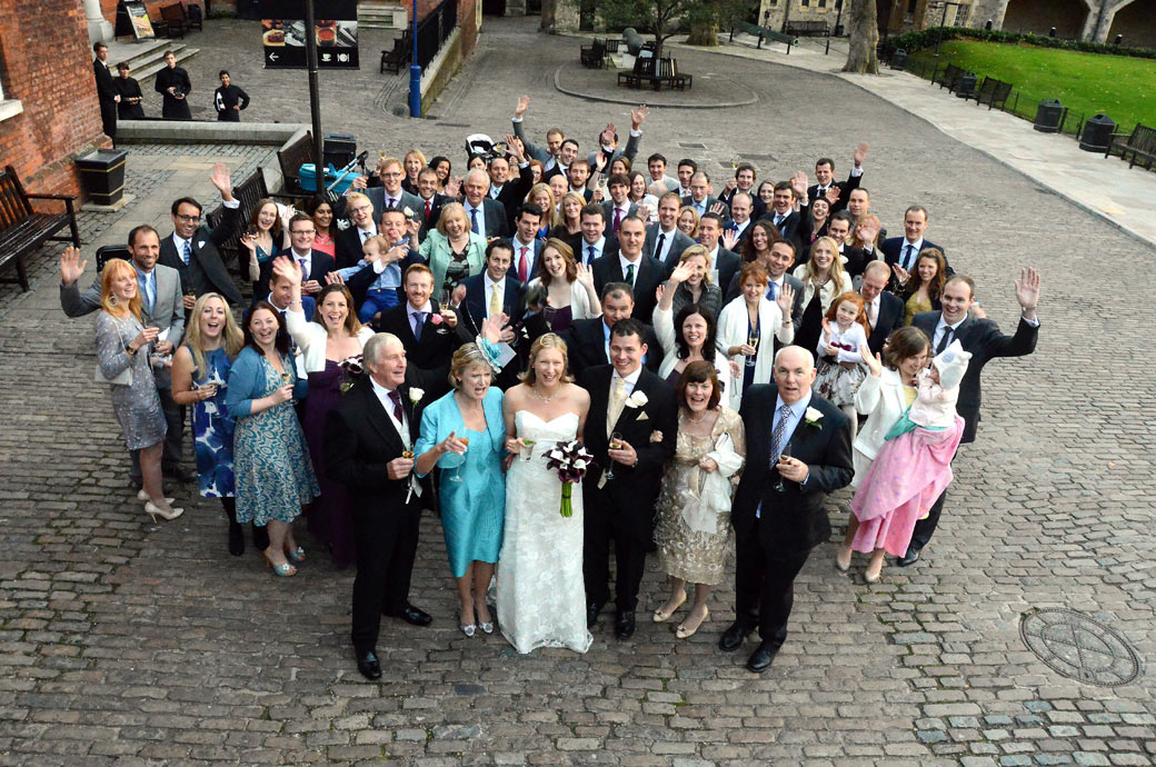 Group wedding photo of all family and guests waving wedding photo taken outside the New Armouries building at the unique London wedding venue at The Tower of London