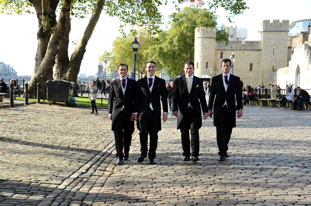Groom and Groomsmen walking on the cobbles wedding photograph taken as they pass the ever popular and spectacular Tower of London a unique London wedding venue