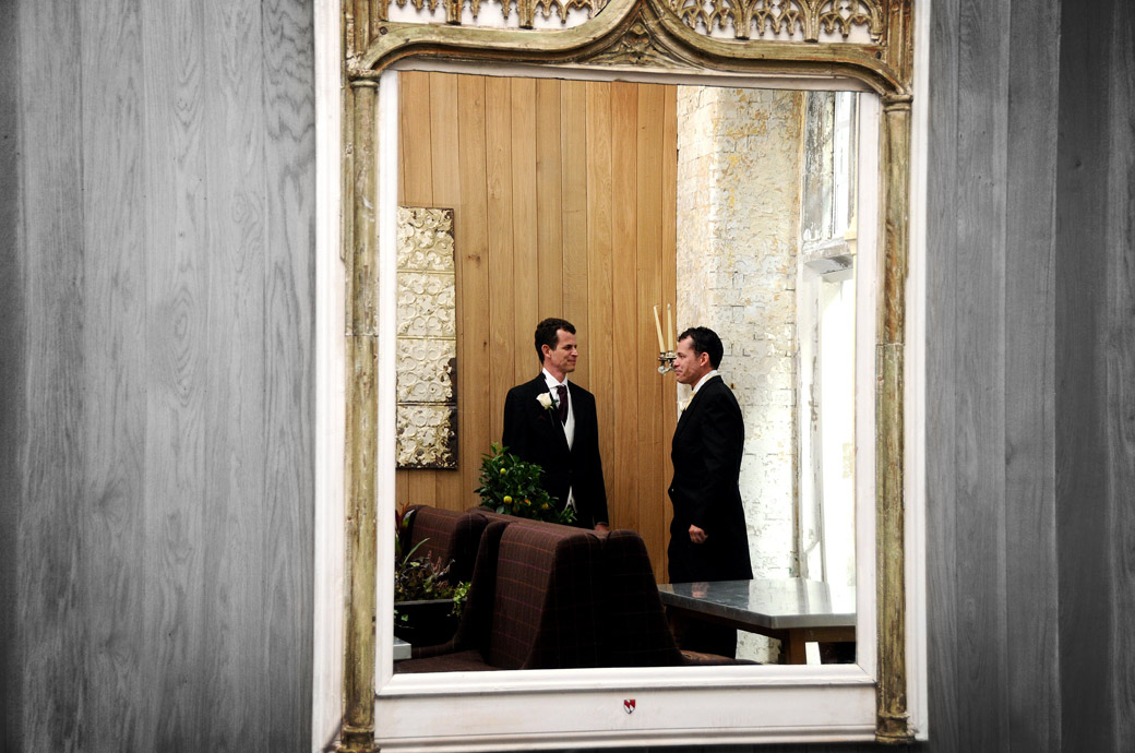 Unusual reflected in a mirror wedding photograph of a Groom talking to his brother in a bar on next to the Thames and a short distance to The Chapel Royal of St Peter ad Vincula at The Tower of London
