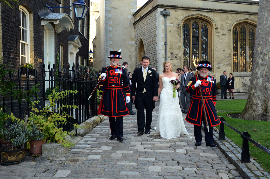 A happy couple with their Beefeater guard in this wedding photo taken as they walk from The Chapel Royal of St Peter ad Vincula at the Tower of London