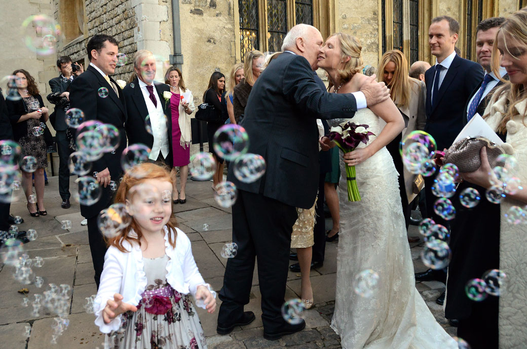 Hugs and kisses amongst the bubbles wedding photograph captured at The Tower of London outside The Chapel Royal of St Peter ad Vincula a unique London wedding venue