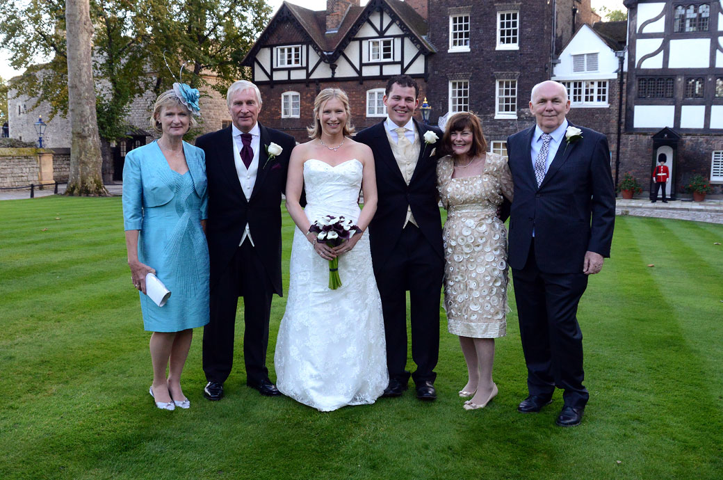 Intimate group family wedding photo taken on the lawn at the spectacular London tourist attraction and unique  London wedding venue of the Tower of London