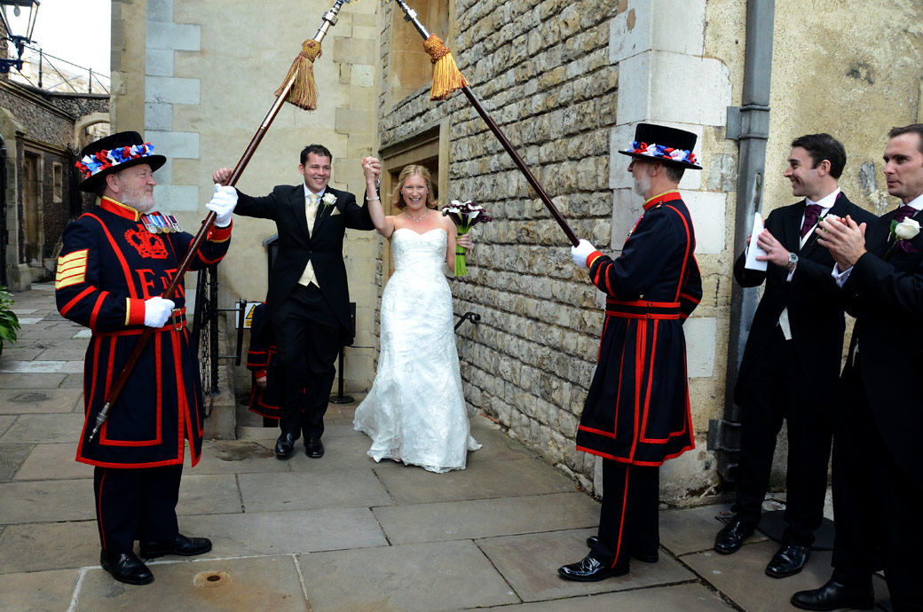 Joyous hands in the air celebrating wedding photographs taken as the newly-weds exit The Chapel Royal of St Peter ad Vincula towards the Beefeaters at The Tower of London