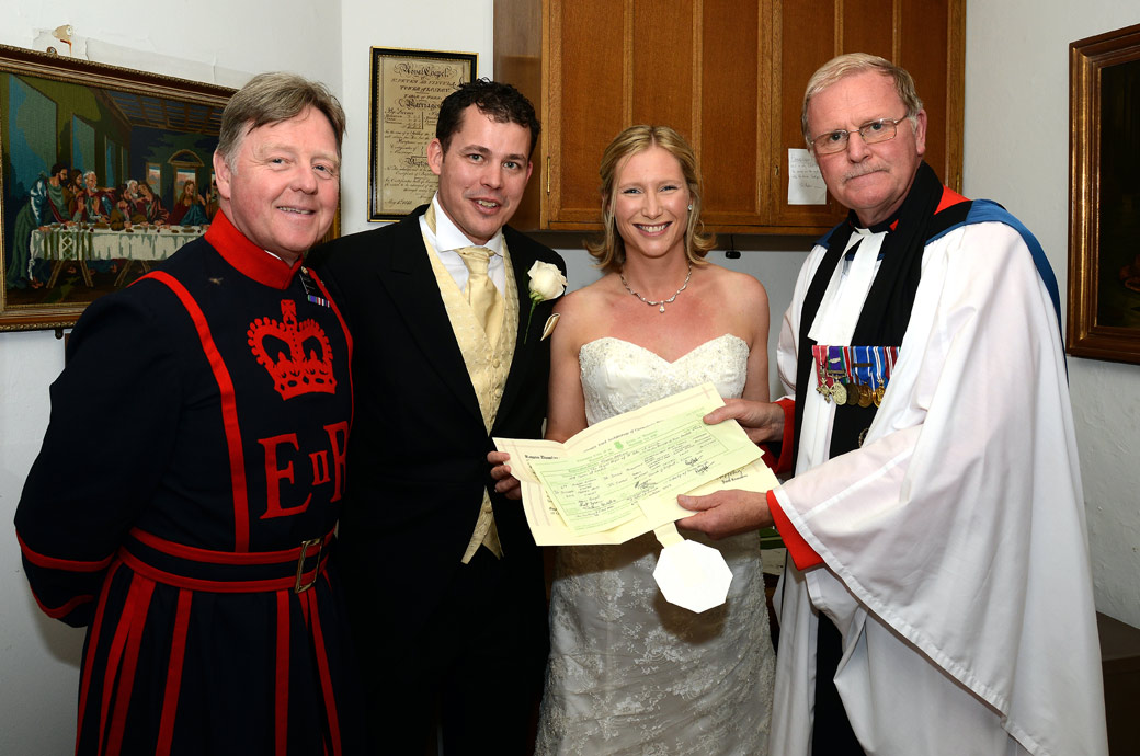 The Chapel Royal of St Peter ad Vincula at The Tower of London is the location for this wedding picture of the newlyweds showing their marriage certificate the vicar and a yeoman of the guard