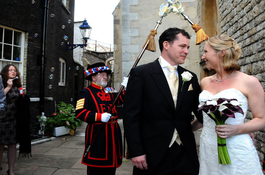 A happy tender loving moment in the bubbles wedding picture taken after walking under the Beefeaters' crossed spears at this unique London wedding venue at the Tower of London