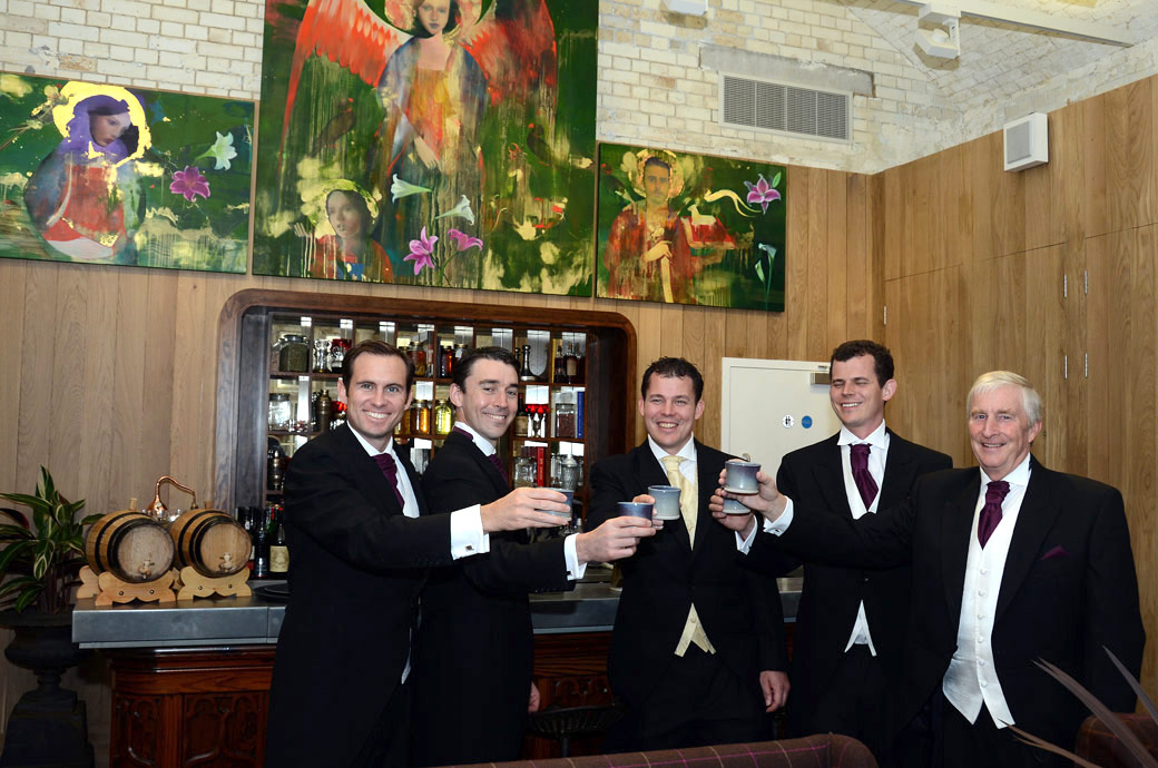 Groom raises an earthenware mug of beer with his Groomsmen in this wedding picture taken to celebrate his forthcoming marriage at the unique and historic Tower of London