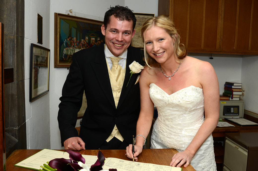 Wedding photograph of a smiling newlywed couple signing the marriage register in The Chapel Royal of St Peter ad Vincula at the unique wedding venue The Tower of London