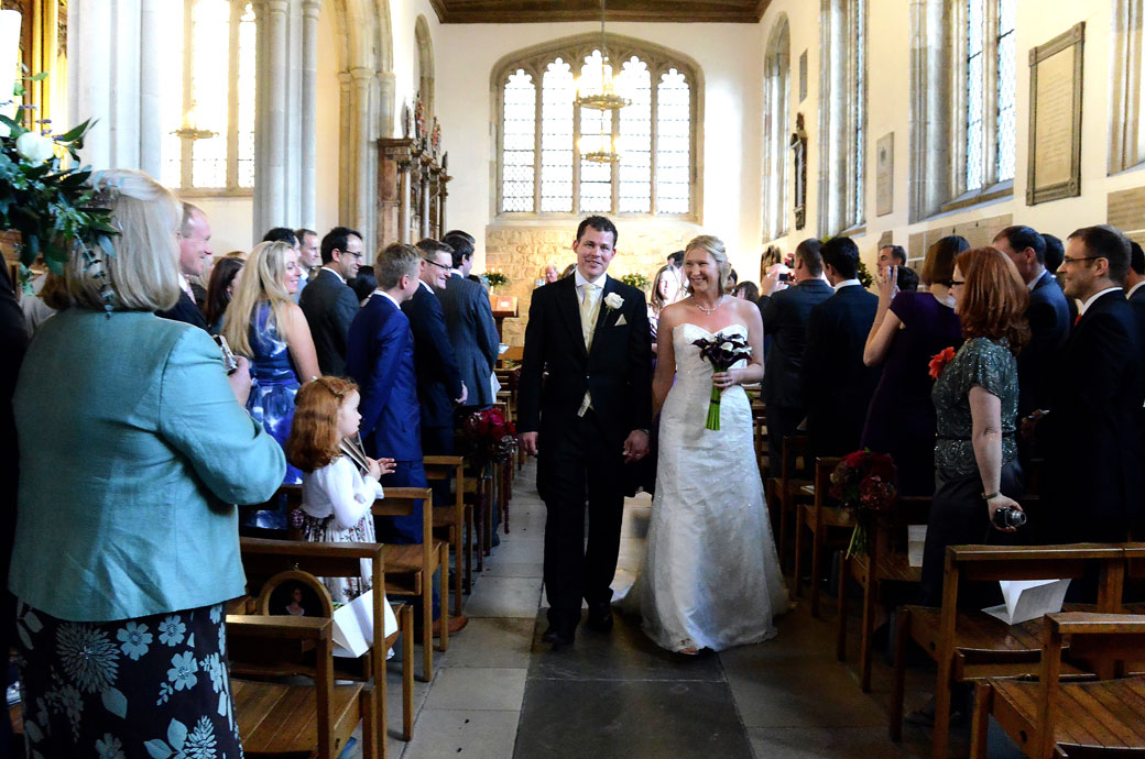 Happy newlyweds captured in this wedding picture as they walk down the aisle of The Chapel Royal of St Peter ad Vincula at The Tower of London as husband and wife