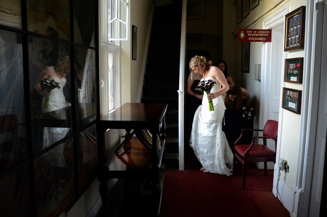 Final Bride's dress adjustments wedding picture taken in the hall of the Armouries Building before leaving for the Chapel Royal of St Peter ad Vincula in The Tower of London