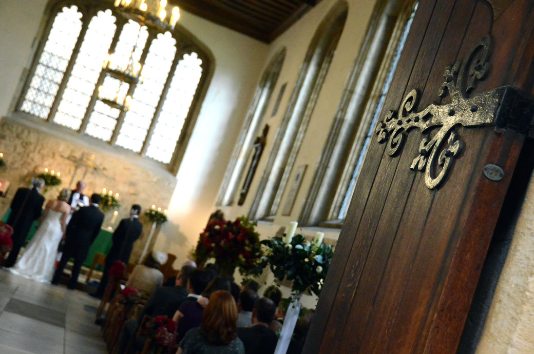 A discrete view from the door wedding photograph of a marriage ceremony in progress at The Tower of London taking place in the ancient Chapel Royal of St Peter ad Vincula