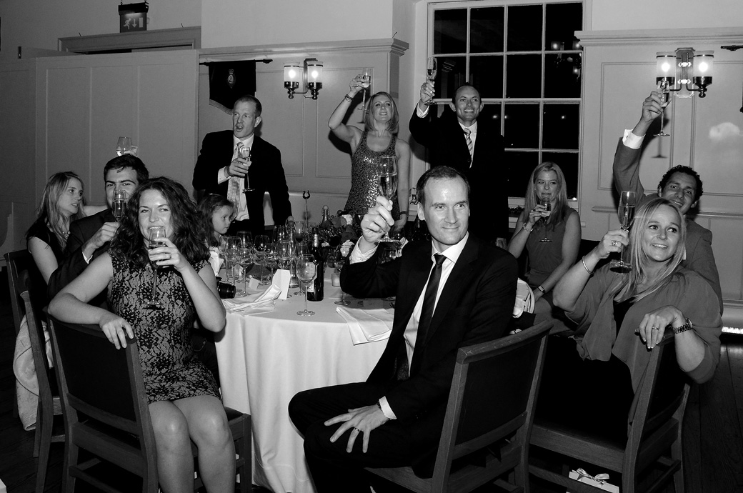 Guests cheering and raising a glass of champagne wedding picture taken during the speeches at The Tower of London wedding venue in the New Armouries Banqueting Suite